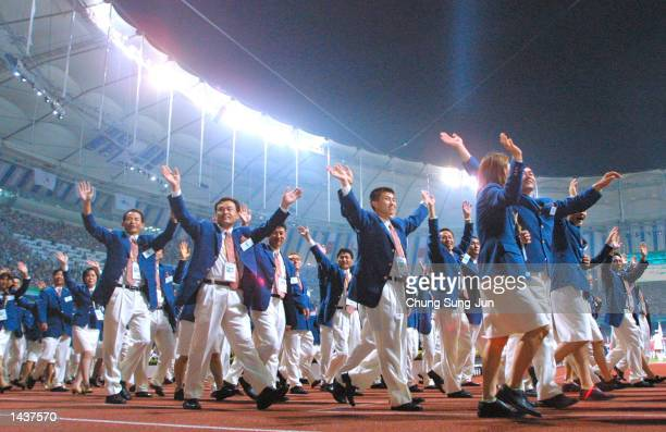 Athletes from divided Koreas march together led by a unification flag during opening ceremonies for the 14th Asian Games September 29 2002 in Busan...