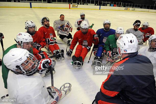 Athletes from the US Paralympic Sled Hockey Team huddle together after practicing shooting drills during the team's practice at the Sertich Ice Arena...
