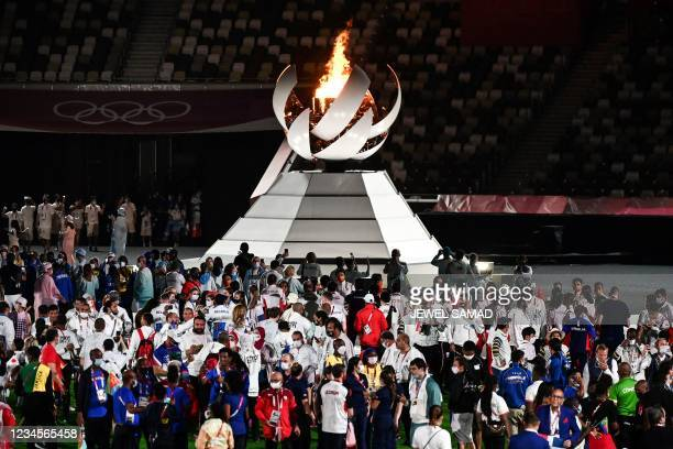 Athletes gather by the The Olympic Cauldron and the Olympic flame to celebrate during the closing ceremony of the Tokyo 2020 Olympic Games, at the...