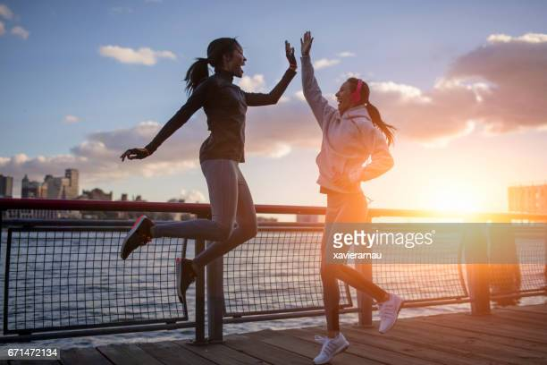 Athletes giving high-five by river during sunset