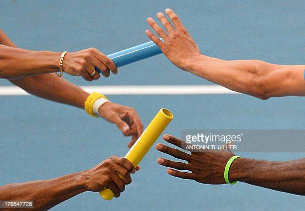 Athletes hand over the baton during the men's 4x400 metres relay at the 2013 IAAF World Championships at the Luzhniki stadium in Moscow on August 15...