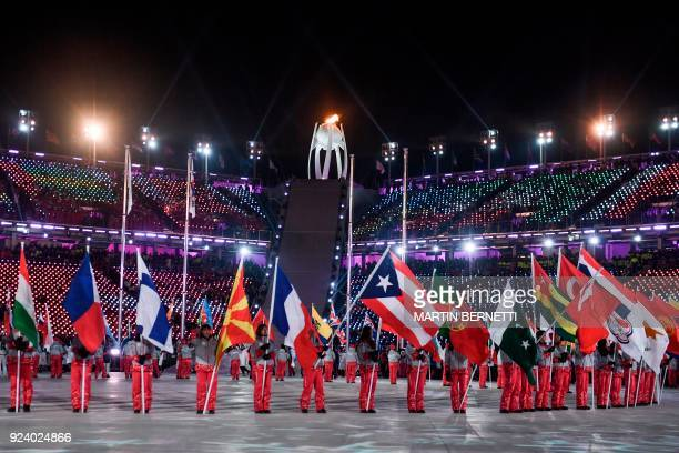 TOPSHOT Athletes hold up their national flags during the closing ceremony of the Pyeongchang 2018 Winter Olympic Games at the Pyeongchang Stadium on...