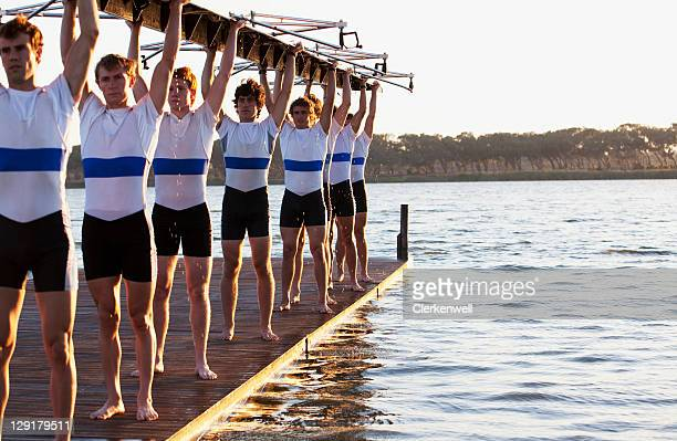Athletes holding a crew canoe over heads