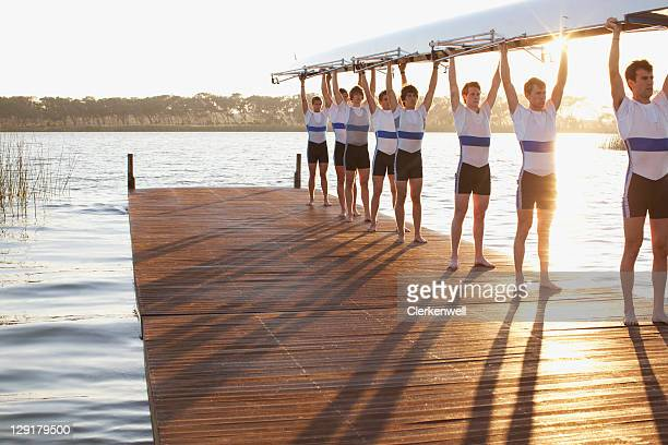 athletes holding their boat upwards - team sport stock pictures, royalty-free photos & images