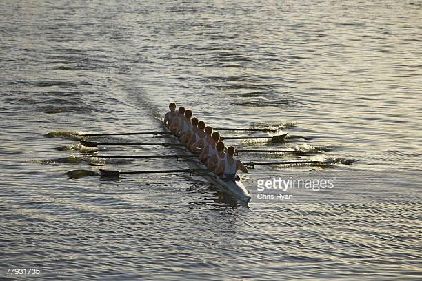 Atletas en una fila de botes midstroke tripulación