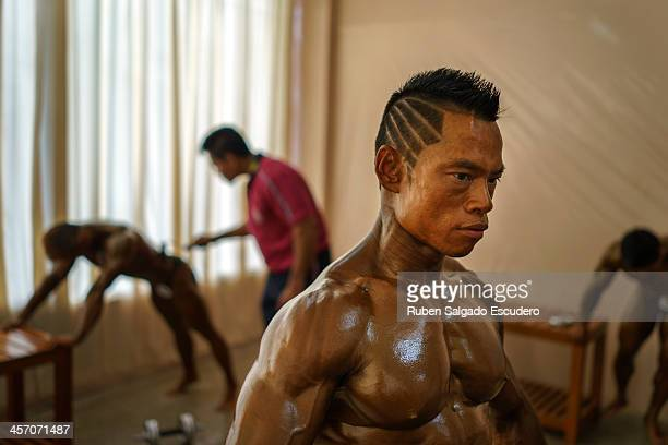 Athletes in the 55kg category get ready to compete in the bodybuilding contest at the Myanmar Convention Center during the 2013 SEA Game on December...