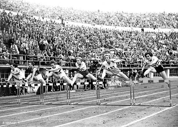 Athletes jump a hurdle in the final of the 80m hurdles Helsinki olympics 26 July 1952 Australian athlete de la Hunty won the gold medal She also took...
