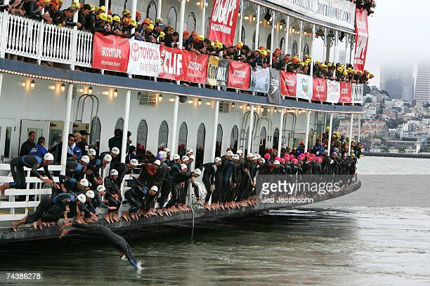Athletes jump into the San Francisco Bay in front of Alcatraz island at the start of the Escape from Alcatraz Triathlon on June 3 2007 in San...
