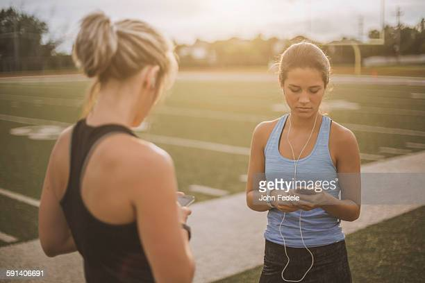 Athletes listening to mp3 players on sports field