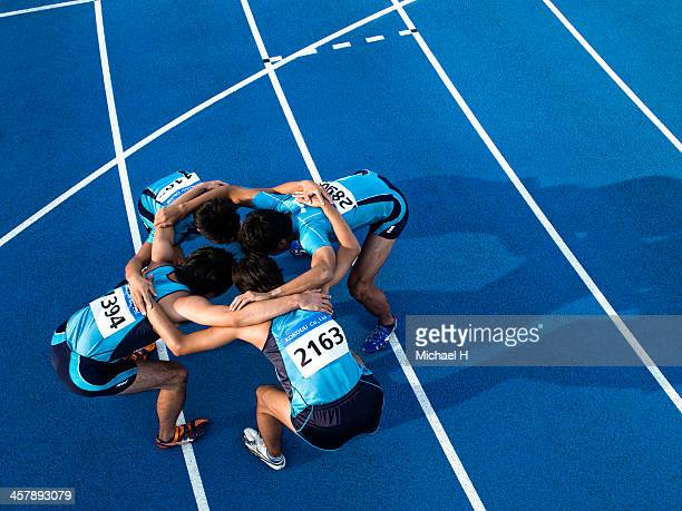 athletes making a circle - sportmannschaft stock-fotos und bilder
