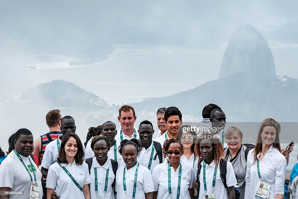 Athletes of the Refugee Olympic Team (ROT) pose for media with the view of Sugarloaf mountain and Guanabara bay (background) ahead of Rio 2016 Olympic games in Rio de Janeiro, Brazil, on July 30, 2016. The International Olympic Committee (IOC) selects 10 refugee athletes to set a refugee's team for the first time, to bring about hope to people displaced by conflicts or war in the world. / AFP / YASUYOSHI