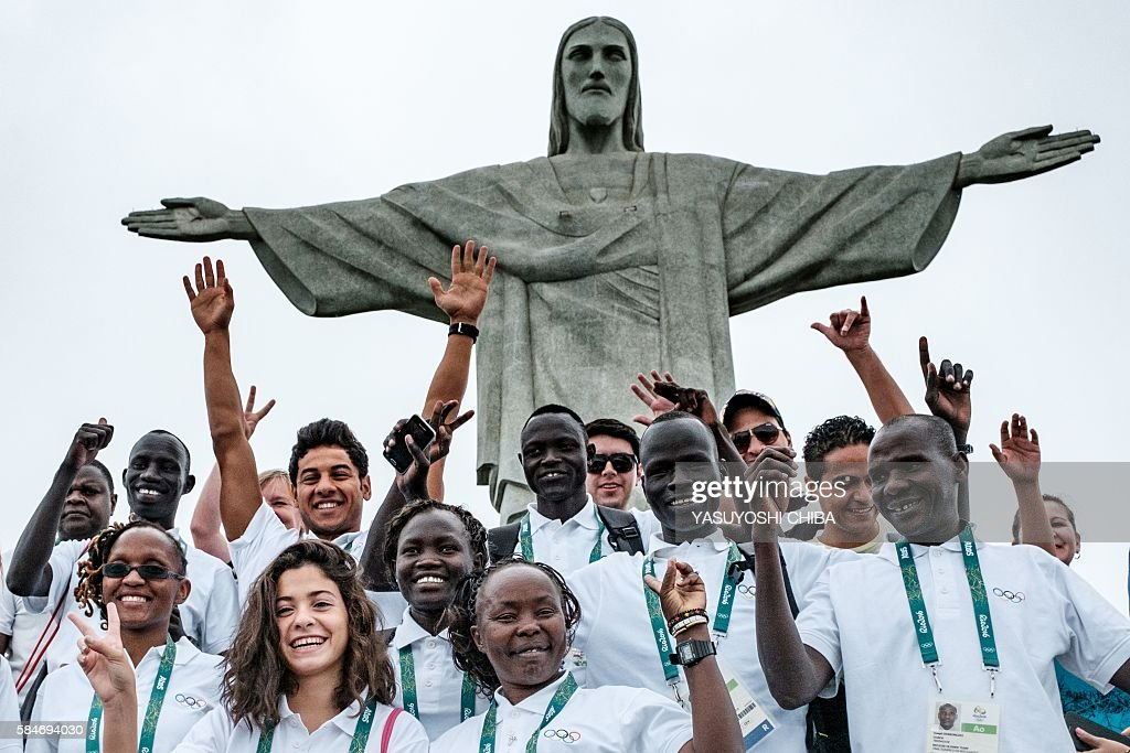 Athletes of the Refugee Olympic Team (ROT) take pictures with a staffer in front of the statue of Christ the Redeemer as the statue appears in fog ahead of Rio 2016 Olympic games in Rio de Janeiro, Brazil, on July 30, 2016. The International Olympic Committee (IOC) selects 10 refugee athletes to set a refugee's team for the first time, to bring about hope to people displaced by conflicts or war in the world. / AFP / YASUYOSHI