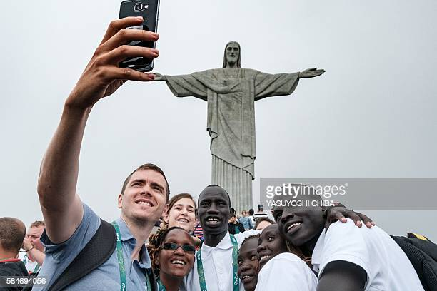 Athletes of the Refugee Olympic Team take pictures with a staffer in front of the statue of Christ the Redeemer as the statue appears in fog ahead of...