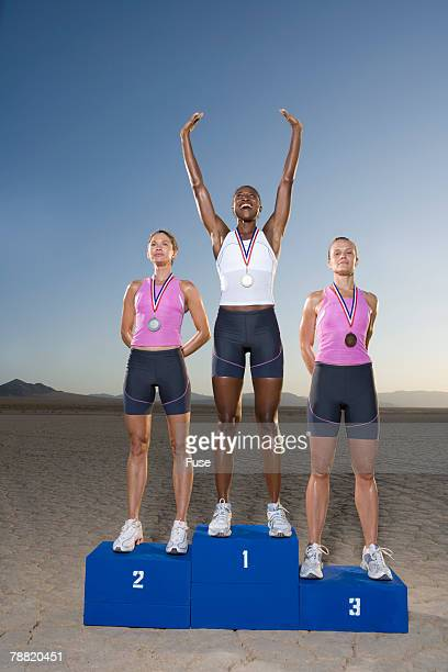 athletes on winner's podium - winners podium stock pictures, royalty-free photos & images