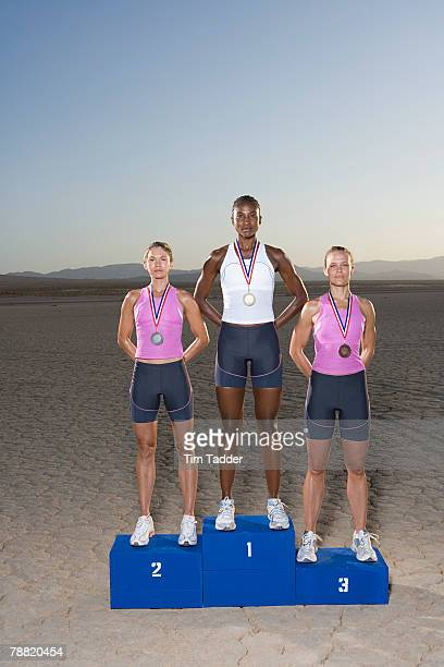 athletes on winner's podium - medalist stock photos and pictures