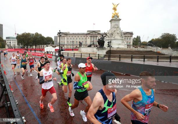 Athletes pass Buckingham Palace and the Queen Victoria Memorial during the Virgin Money London Marathon around St James' Park.