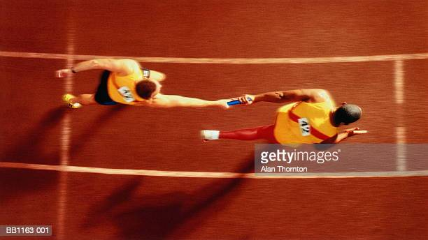 athletes passing baton in relay  race, overhead, (digital composite) - passing sport imagens e fotografias de stock