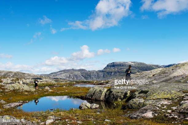 Athletes passing one of the many lakes at Hardangervidda Marathon on September 2 2017 in Eidfjord Norway Hardangervidda Marathon goes through parts...