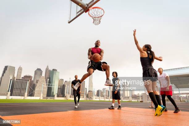 athletes playing basketball in court against buildings - デイフェンス ストックフォトと画像