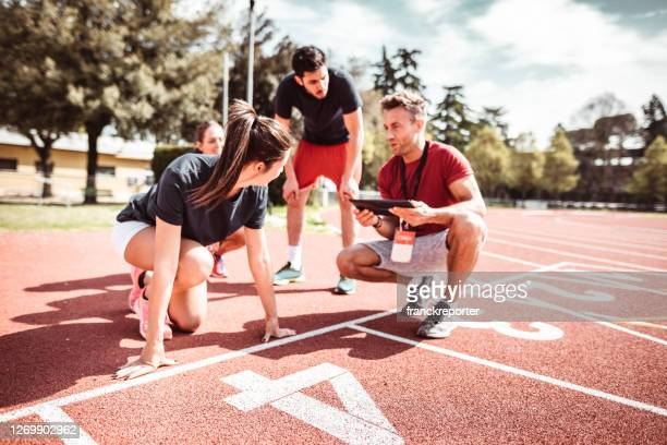 athletes reading to start on the track - coach stock pictures, royalty-free photos & images