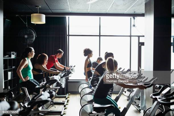 Athletes riding indoor bikes during class in cycling studio