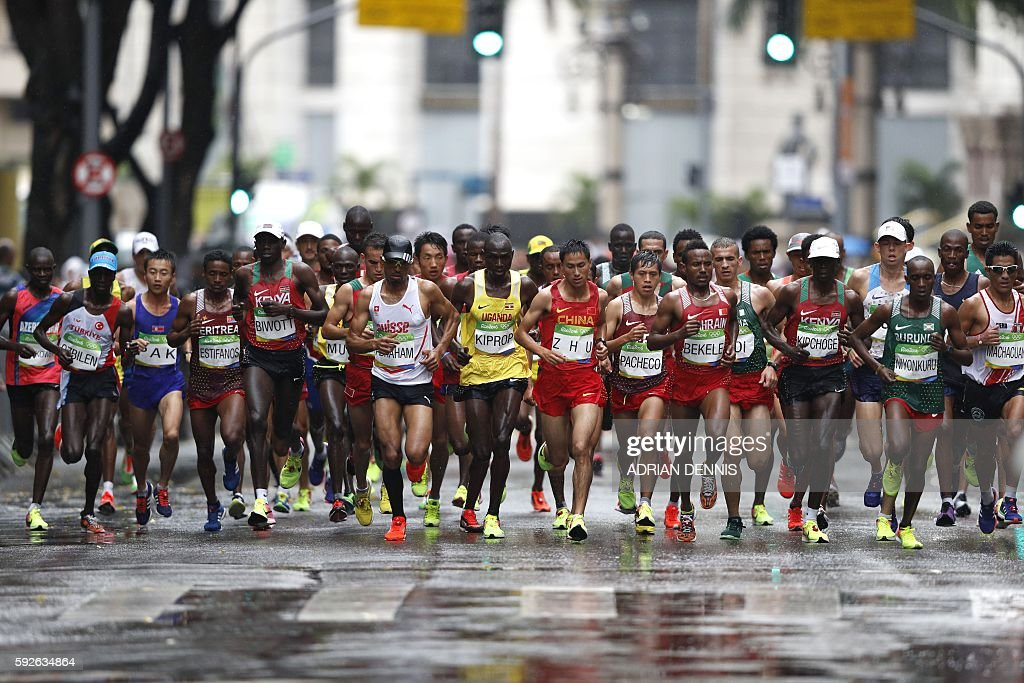 TOPSHOT - Athletes run during the Men's Marathon athletics event at the Rio 2016 Olympic Games in Rio de Janeiro on August 21, 2016. / AFP / Adrian DENNIS