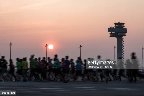 TOPSHOT Athletes run over the grounds of the future BER Berlin Brandenburg Airport under construction in Schoenefeld near Berlin eastern Germany...