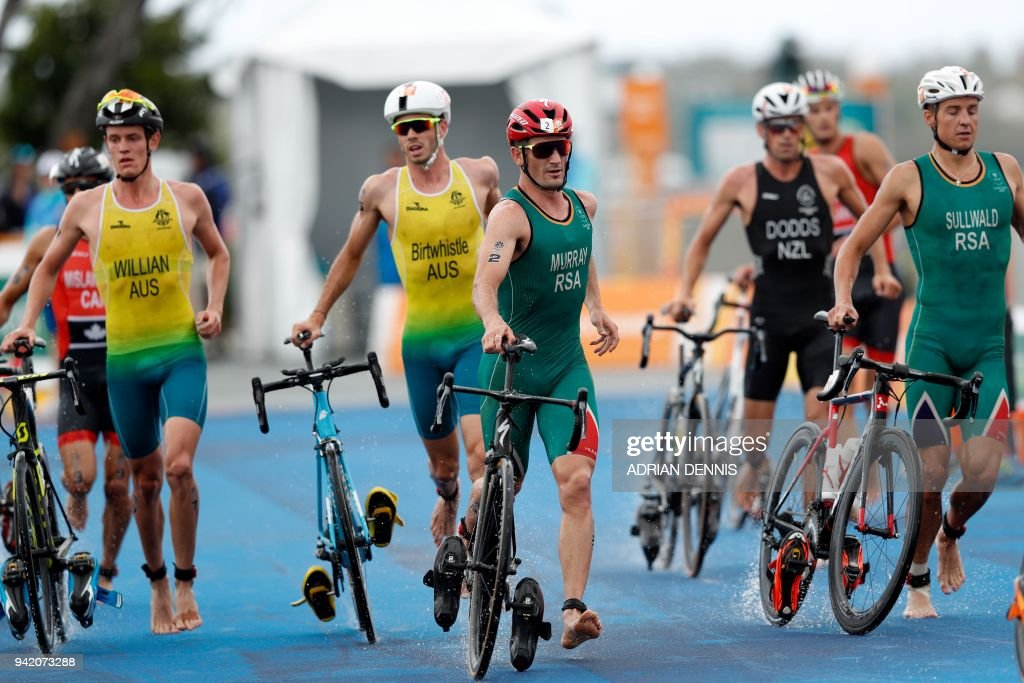 TOPSHOT - Athletes run with their bicycles through the transition area during the mens triathlon final during the 2018 Gold Coast Commonwealth Games at the Southport Broadwater Parklands venue in Gold Coast on April 5, 2018. /