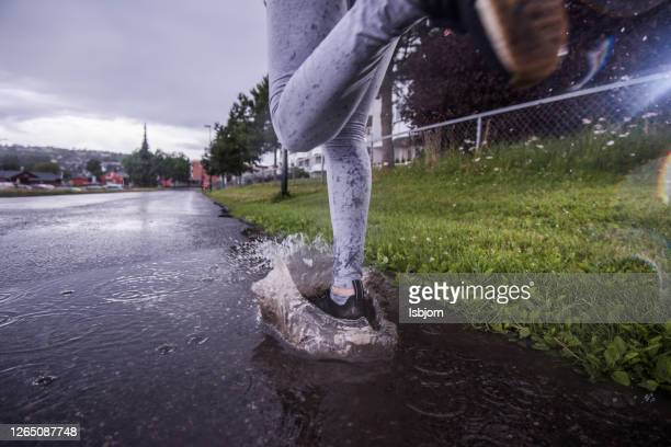 athletes running at rainy day, close-up. - active lifestyle stock pictures, royalty-free photos & images