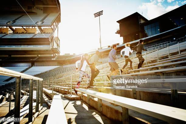 Athletes running stairs during workout in stadium