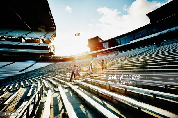 athletes running stairs in empty stadium at sunset - forward atlet bildbanksfoton och bilder