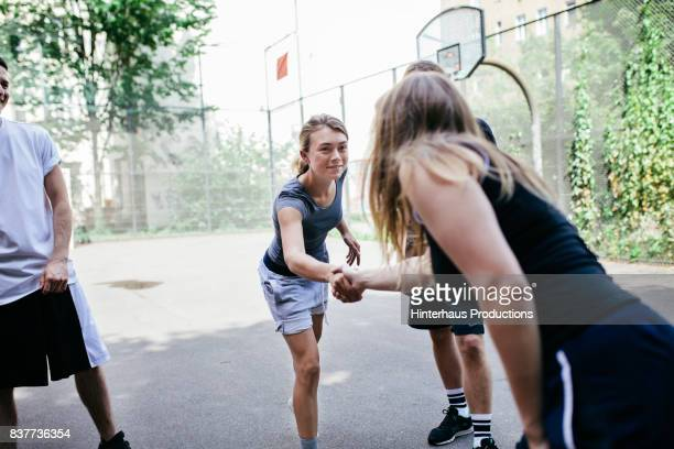 Athletes Shaking Hands Before Friendly Game Of Basketball Outdoors