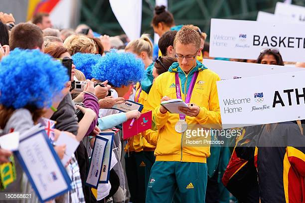 Athletes sign autographs during the Australian Olympic Team Homecoming Parade at Federation Square on August 22 2012 in Melbourne Australia
