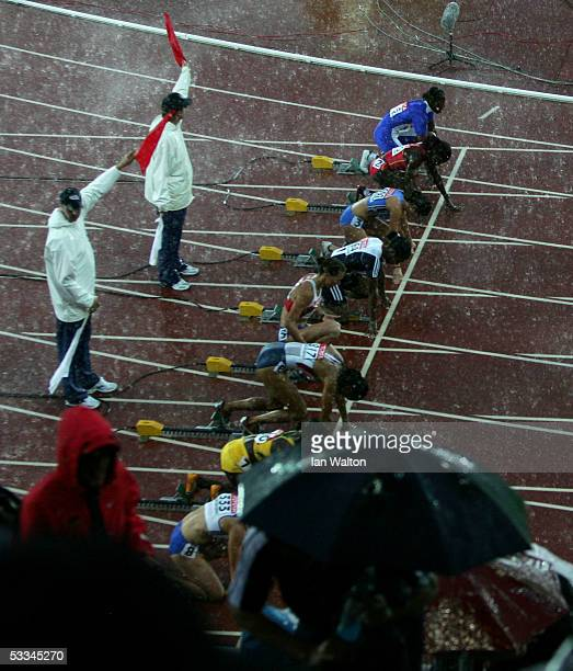 Athletes stand in the rain as they wait for the start of the women?s 100 metres Hurdles at the 10th IAAF World Athletics Championships on August 9,...