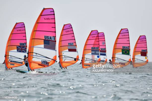 Athletes take part in the women's windsurfing RSX class competition during a sailing test event for the Tokyo 2020 Olympic Games off the coast...