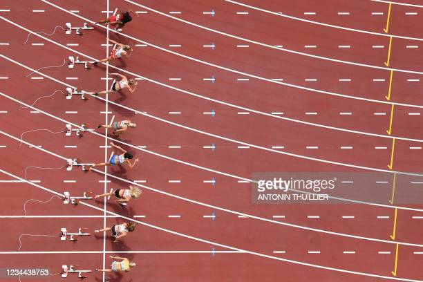 Athletes take the start in the women's heptathlon 100m hurdles during the Tokyo 2020 Olympic Games at the Olympic Stadium in Tokyo on August 4, 2021.