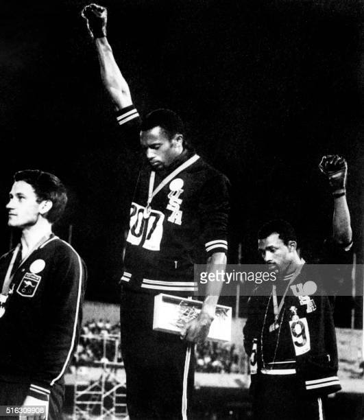 Athletes Tommie Smith and John Carlos raise their gloved fists in the Black Power salute to express their opposition to racism in the USA during the...