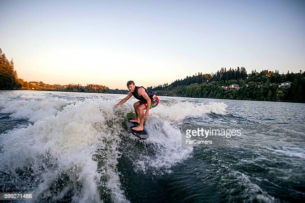 Athletic adult male wake surfing