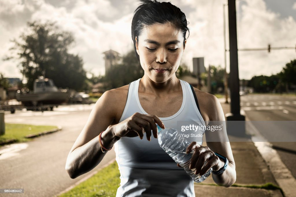 Athletic Asian Woman Drinking Water in town