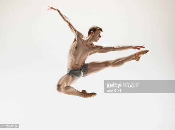 Athletic ballet dancer in a perfect shape performing over the grey background