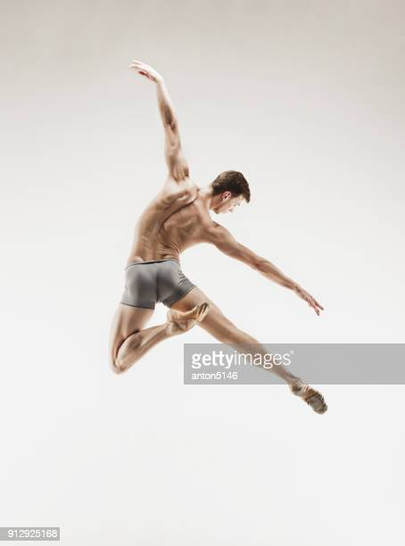 athletic ballet dancer in a perfect shape performing over the grey background - male ballet dancer stock photos and pictures