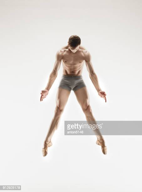 athletic ballet dancer in a perfect shape performing over the grey background - art modeling studios stock photos and pictures