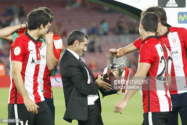 Athletic Bilbao's coach Ernesto Valverde looks at the Supercup trophy after the Spanish Supercup secondleg football match FC Barcelona vs Athletic...