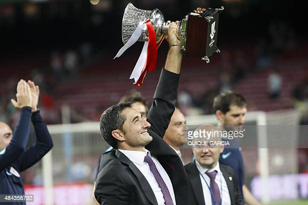 Athletic Bilbao's coach Ernesto Valverde raises the Supercup trophy after the Spanish Supercup secondleg football match FC Barcelona vs Athletic Club...