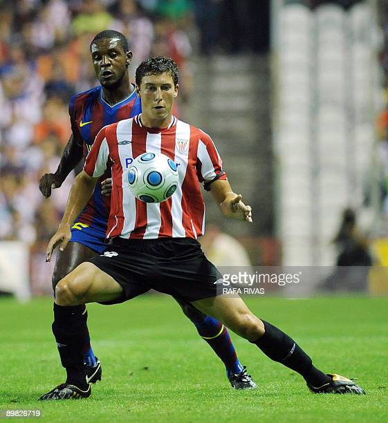 Athletic Bilbao's De Marcos vies with Barcelona's French Eric Abidal during their Spanish Supercup 1st leg football match on August 16 at San Mames...