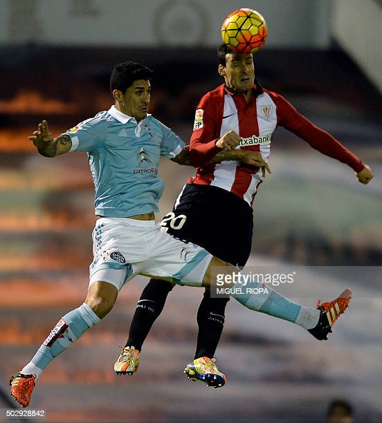 Athletic Bilbao's forward Aritz Aduriz heads the ball past Celta Vigo's Chilean midfielder Pablo Hernandez during the Spanish league football match...