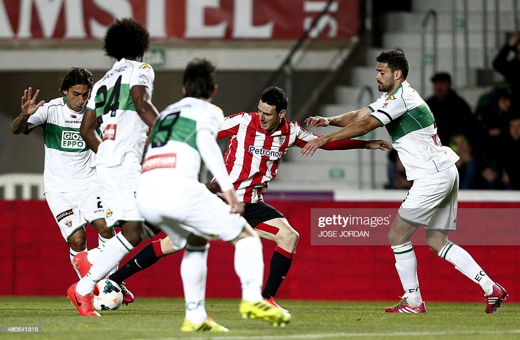 Athletic Bilbao's forward Aritz Aduriz (L) vies with Elche's defender Botia during the Spanish league football match Elche CF vs Athletic Club Bilbao at the Martinez Valero stadium in Elche on March 25, 2014.