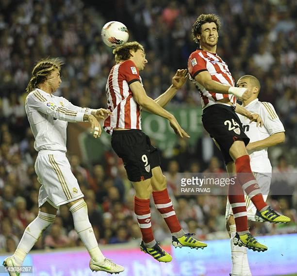 Athletic Bilbao's forward Fernando Llorente heads the ball between Athletic Bilbao's midfielder Javi Martinez and Real Madrid's defender Sergio Ramos...