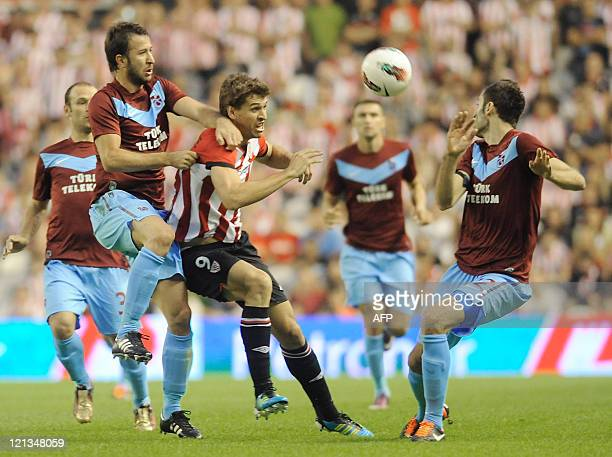 Athletic Bilbao's forward Fernando Llorente vies for the ball with Trabzonspor's Kacar and Yumlu during a Euroleague football match Athletic Bilbao...