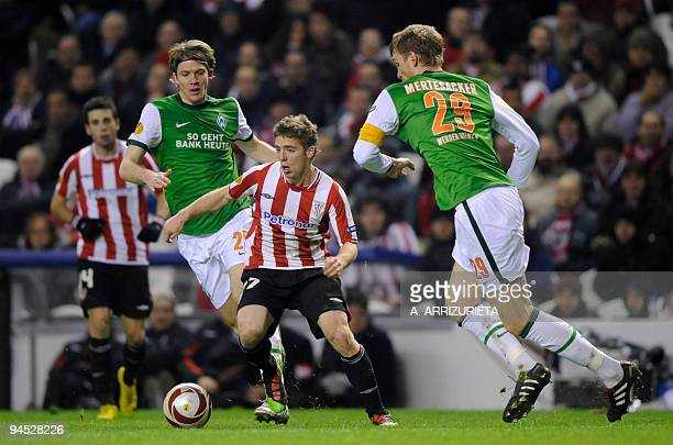 Athletic Bilbao«s forward Iker Muniain vies for the ball with Werder Bremen's German player Per Mertesacker and German player Peter Niemeyer during a...